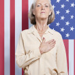 Senior woman against American flag — Stock fotografie