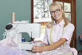 Happy senior woman sewing — Stock Photo
