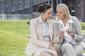 Businesswomen  sitting against office building — ストック写真