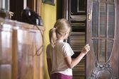 Girl opening cupboard door — Stok fotoğraf
