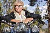 Senior woman leaning on motorbike — Stock Photo