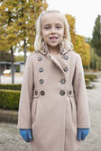 Girl in winter coat standing at park — Stock Photo