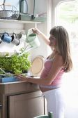 Pregnant woman watering house plants — Foto de Stock