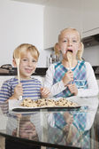 Boy with sister tasting spatula mix — Stock Photo