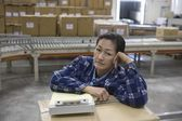 Bored woman in distribution warehouse — Stock Photo