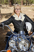 Senior woman sits on motorbike — Stock Photo