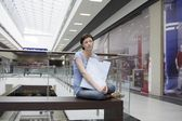 Young woman sits in new Voronezh shopping centre — Stock Photo