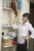 Housekeeper dusting shelf — Stock Photo