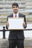 Indian businessman holding blank sign — Stock Photo