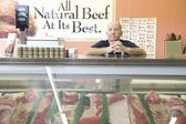 Supermarket employee sharpening knife at meat — Stock Photo