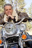 Senior man leaning on motorcycle handlebars — Stock Photo