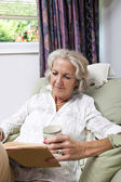 Senior woman with coffee cup reading book — Stock Photo