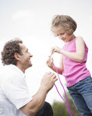 Father and daughter with skipping rope — Stock Photo