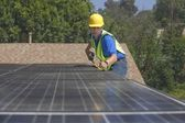 Maintenance worker measures solar array on rooftop — Stock fotografie