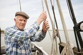 Elderly man holds ropes of sailing boat — Stock Photo