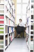 Young woman sits at desk in library — Stock Photo