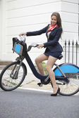 Businesswoman standing with bicycle — Photo
