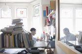 Mitte erwachsener Mann arbeitet in unübersichtlich Studie — Stockfoto