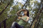 Young woman stands shielding eys with bicycle in woodland — Stock Photo