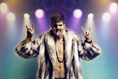 Man in fur coat making rebellious gestures — Stock Photo