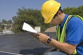 Maintenance worker makes notes with solar array on rooftop — Stock fotografie