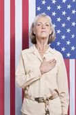 Senior woman against American flag — Stock Photo