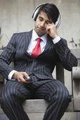 Indian businessman listening music — Stock Photo
