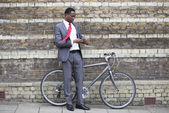 Young businessman with bicycle — Stock Photo