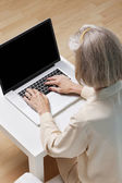 Senior woman surfing the net — Stock Photo