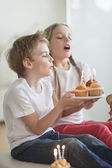 Siblings blowing candles on cupcakes — Stock Photo