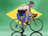 Cyclist cycling in front of Brazilian Flag — Stock Photo