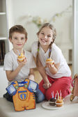 Little boy and girl with cup cakes — Stock Photo