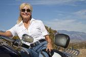 Senior woman sitting on motorcycle — Stock Photo
