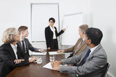 Woman using whiteboard in business meeting — Stock Photo