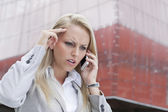 Angry businesswoman conversing on cell phone — Stock Photo