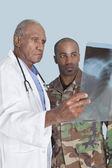 Doctor with soldier looking at x-ray report — Stock Photo