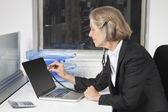 Senior businesswoman examining laptop — Stock Photo