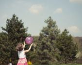 Girl catching purple ball — Stock Photo