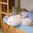 5 year old boy lies on bunk bed with polar bear soft toy — Stock Photo #34011057