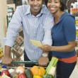 Couple stand with grocery shopping — Stock Photo #34011957
