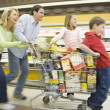 Family run with full shopping trolley — Stock Photo #34012159