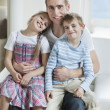 Children sitting on father's laps — Stock Photo #34014353