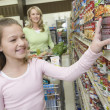 Girl choosing products from supermarket shelf — Stock Photo #34014523