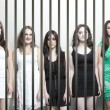 Young women behinds prison bars — Stok fotoğraf