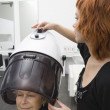Eldelrly woman sits under hairdrying hood — Stock Photo #34016321