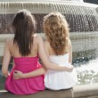 Female friends sitting by fountain — Stock Photo #34016559