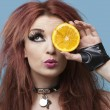 Foto Stock: Funky womcovering eye with orange