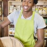 Clerk holding basket of peanuts — Stock Photo #34019997