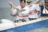 Outrigger canoeing team raise oars — Stock Photo
