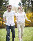 Couple running through park — Stock Photo